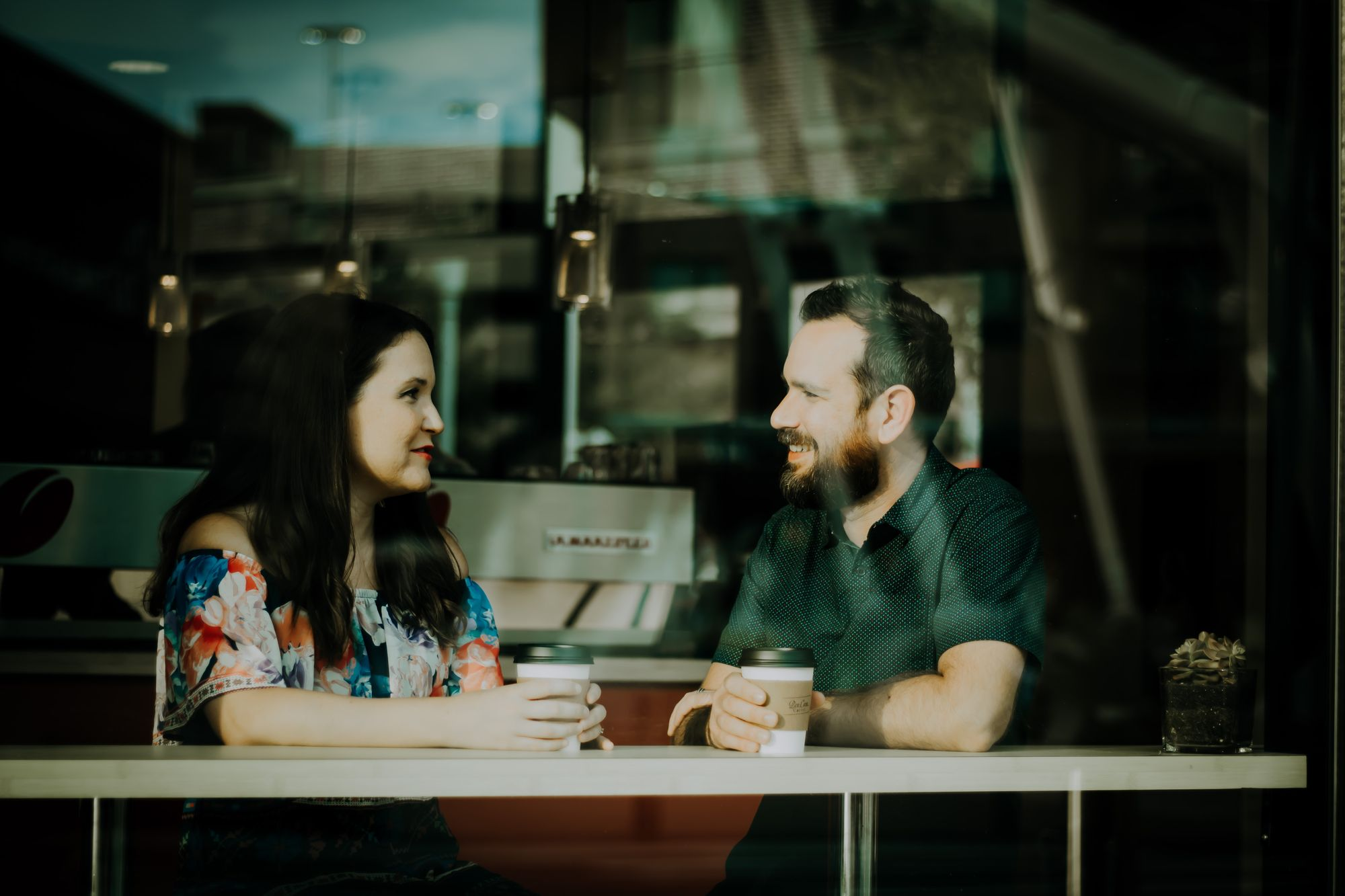 Two coworkers talking over coffee in a cafe.