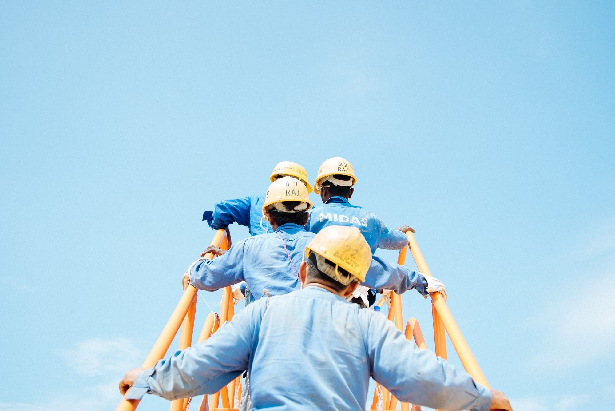 Four industrial workers in blue shirts and yellow hats climb up a yellow staircase