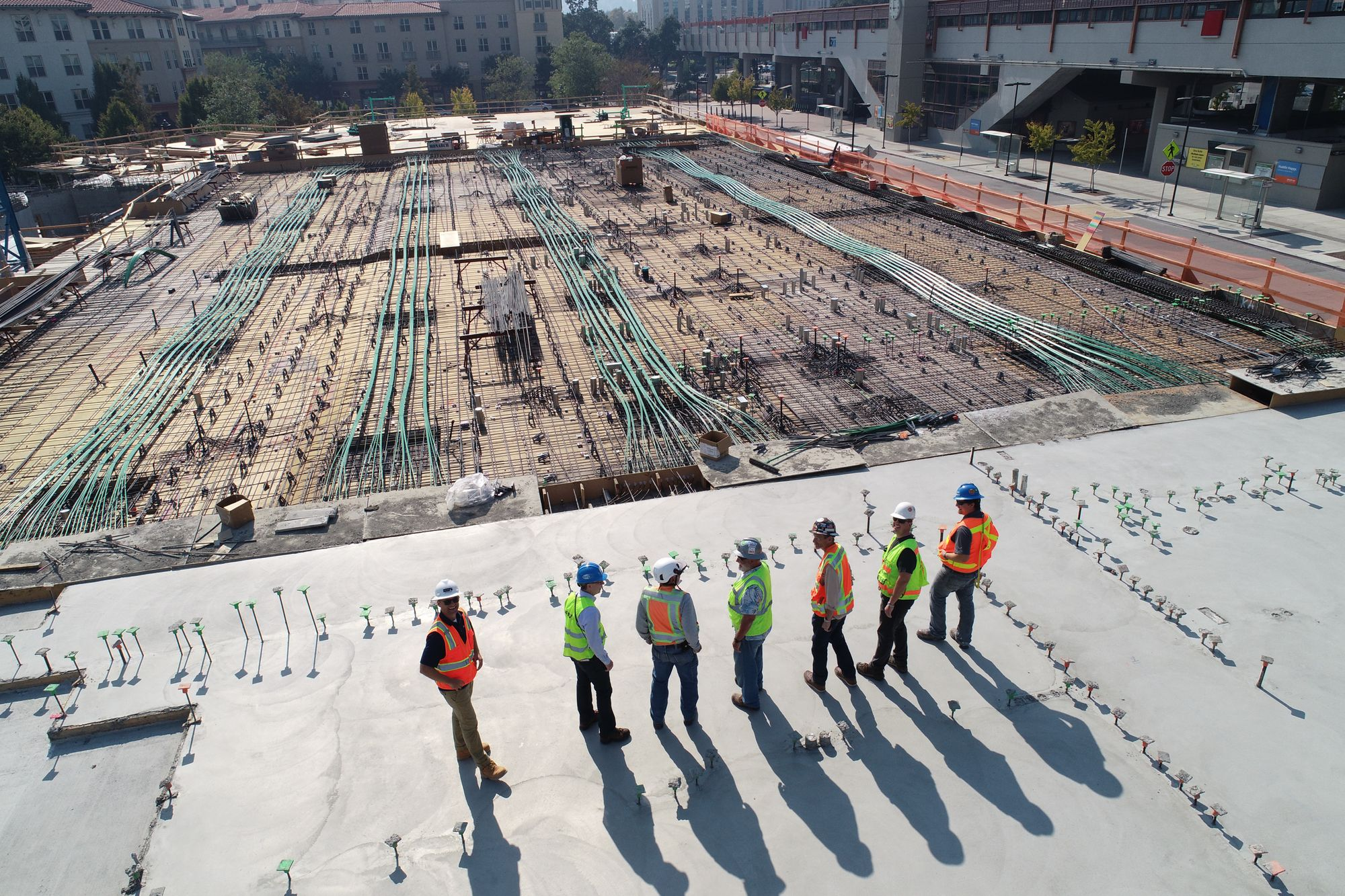 Construction workers stand in a line talking