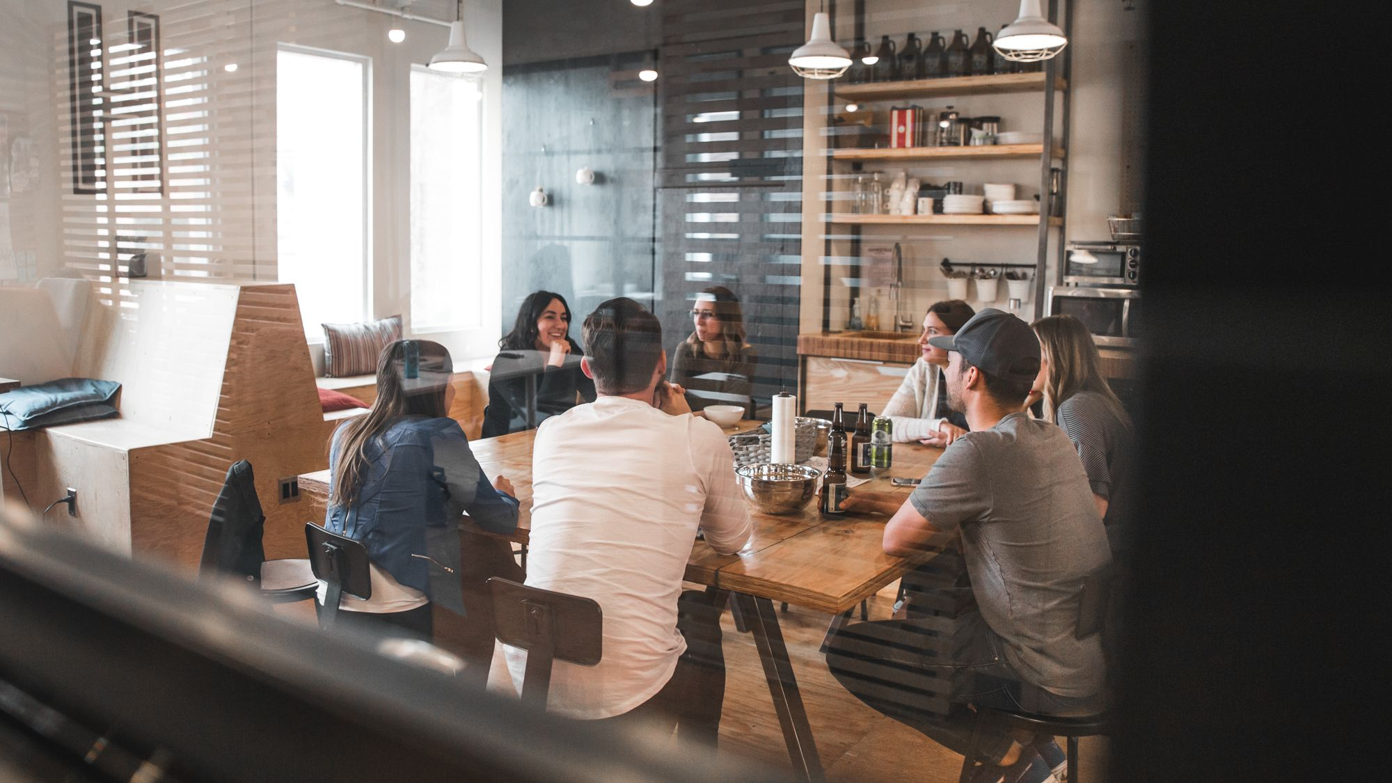 A group of people meet around a table in a restaurant, talking