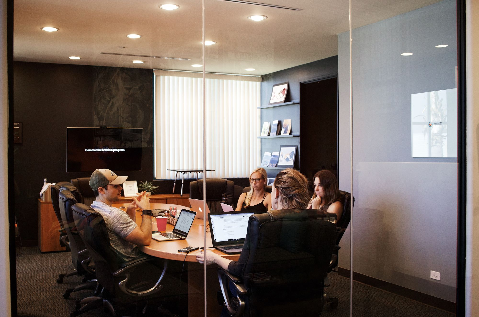Five people sit around a conference room table