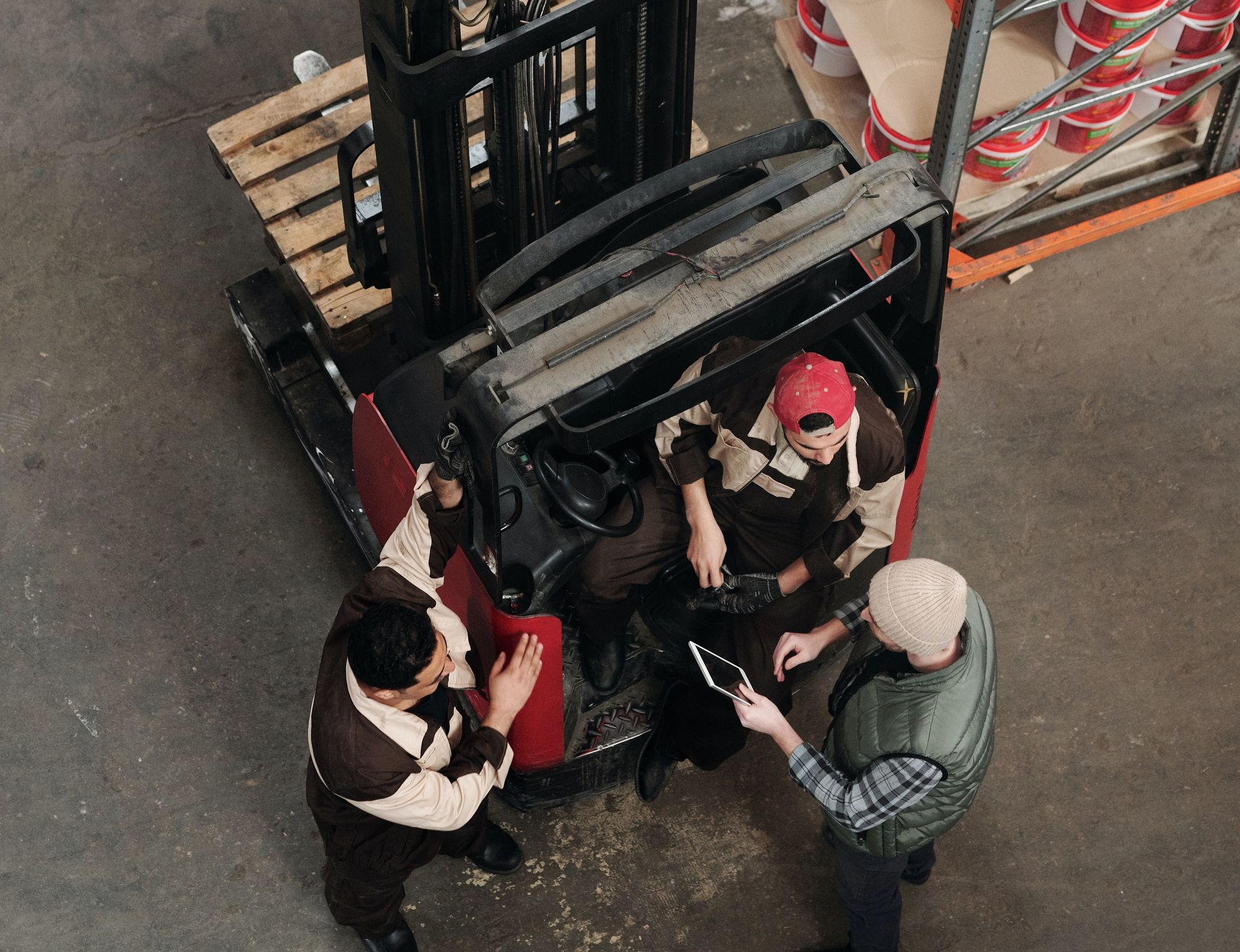 Three men in a warehouse talking with an iPad.