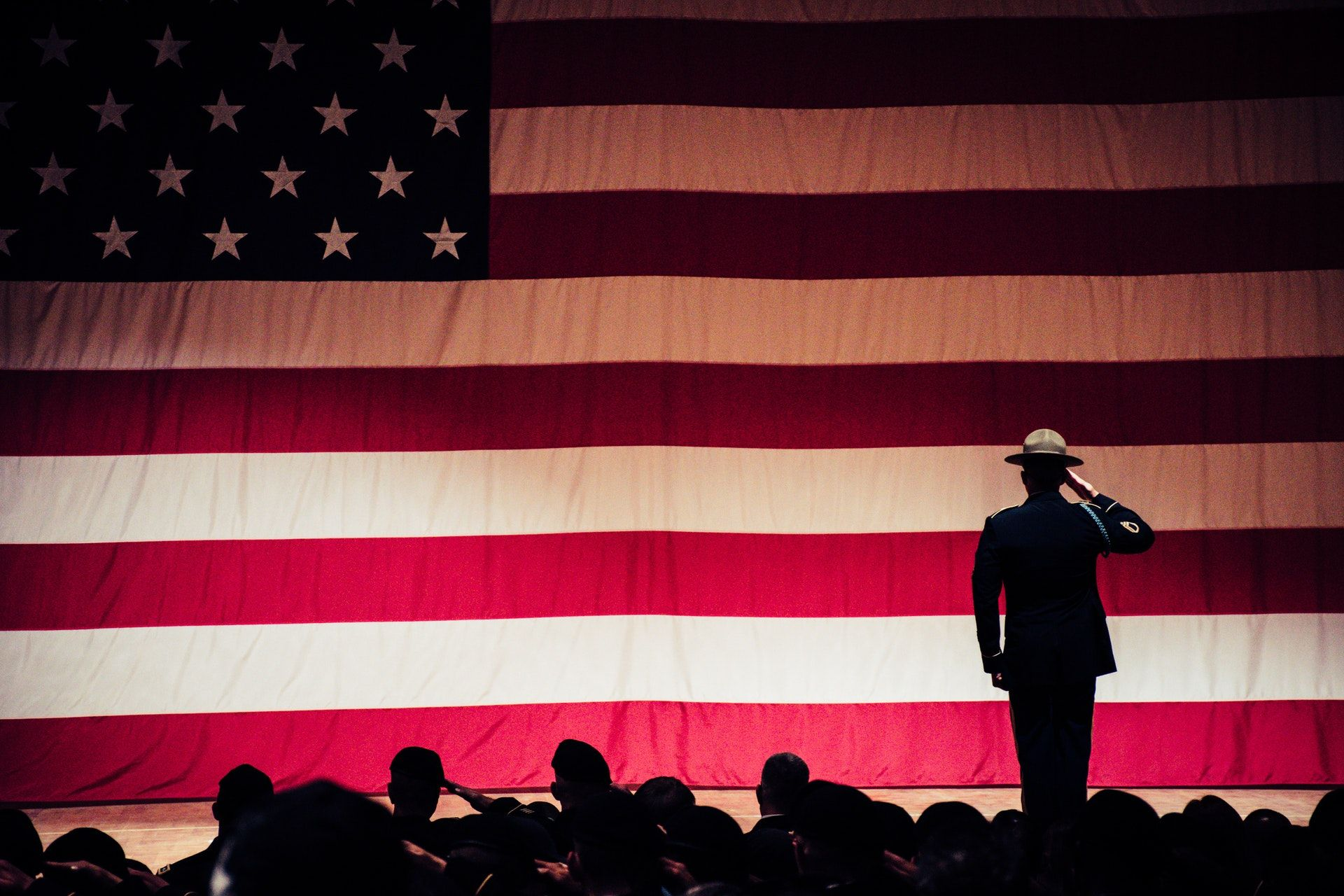 People in silhouette salute a large American flag