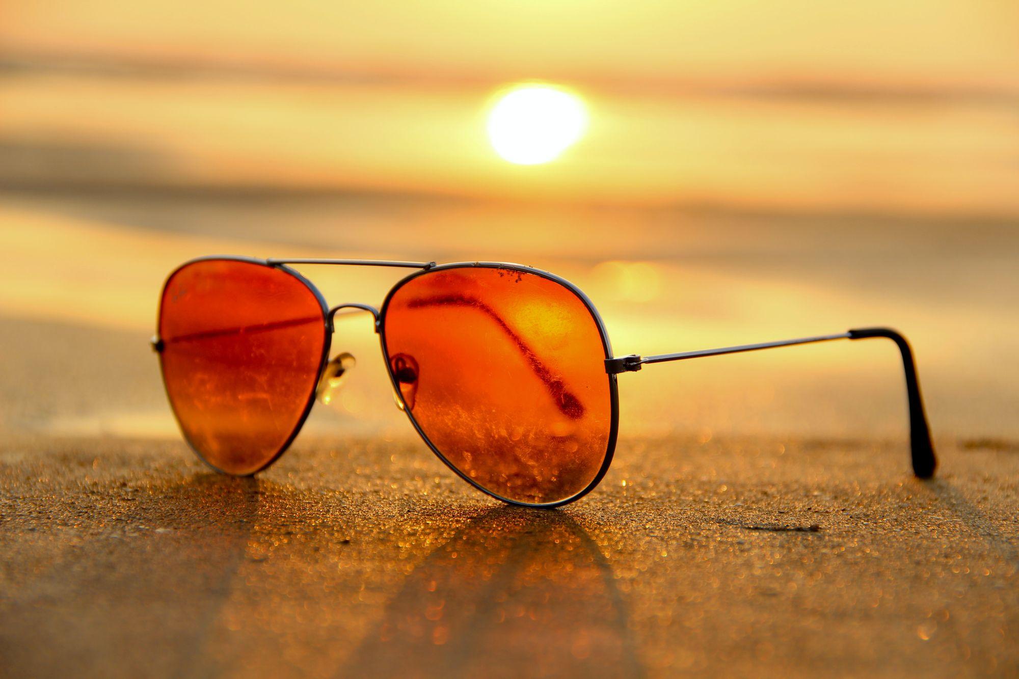 Sunglasses lay on a beech.